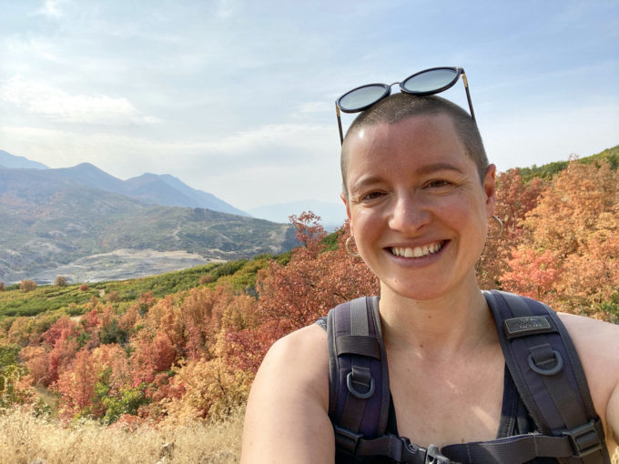 Sarah Dopp is standing on the top of a hill on a hike with autumn leaves in the background. She is wearing a backpack and has sunglasses on top of her head. She is smiling.